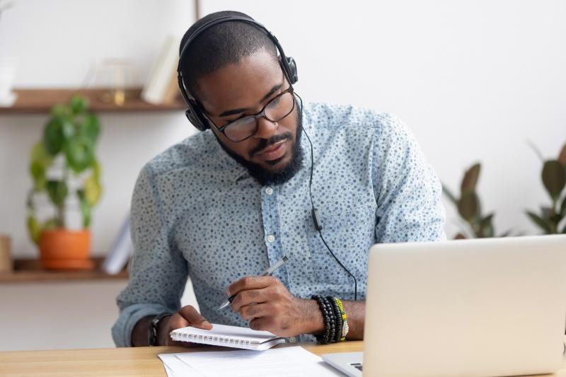 Young man watching a webinar at home